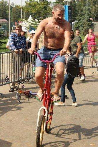 Серьезный дядя на шуточном велосипеде